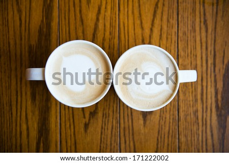two cups of coffee cappuccino with heart shape - stock photo