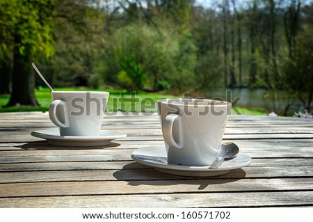 Two cups of coffee in outdoor setting  - stock photo
