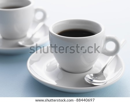 Two cups of coffee on blue background - stock photo