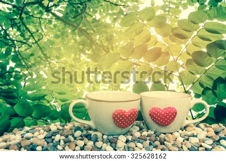two cups of coffee on pebble ground with leaf on tree ,orange and yellow light background ,vintage tone - stock photo