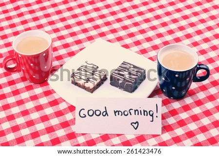 Two cups of coffee on the table. Morning coffee and cake. Plate with sweets and a cup of latte. Good Morning. Note Good morning, surprise, a romantic dinner. Cake with icing. - stock photo