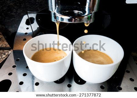 Two cups of coffee that goes down from machine coffee bar - stock photo