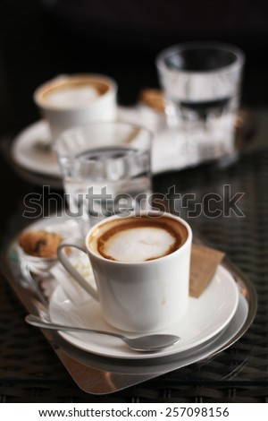 Two cups of coffee with milk in a Viennese coffee house (Wiener Kaffeehaus) served with glass of water and a cookie - stock photo