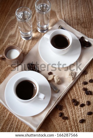 Two cups of dark coffee, milk, water, sugar, spoons, coffee beans, wooden background
