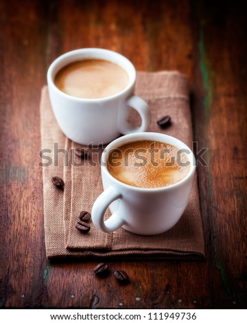 Two cups of espresso on brown napkin - stock photo