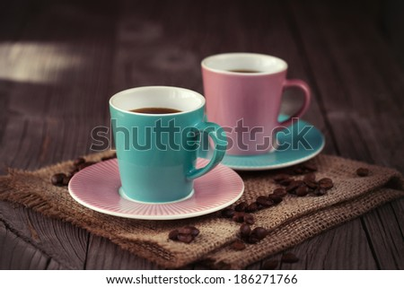 Two cups of espresso with coffee beans on dark wooden background, selective focus - stock photo
