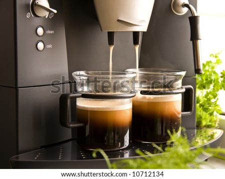 Two cups of fresh coffee with foam made with a coffee machine - stock photo