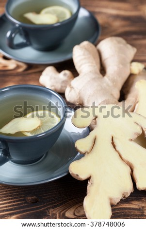 Two cups of ginger tea with a slice of ginger and lemon. Shallow dof - stock photo