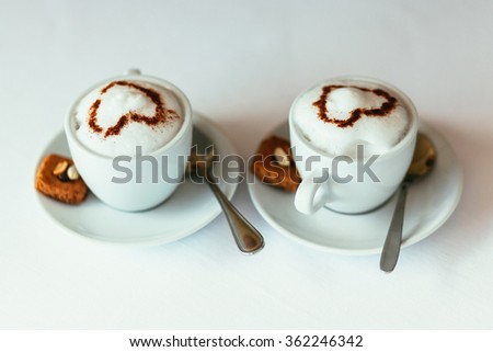 Two cups of gourmet coffee house cappuccino with cookies against a white background