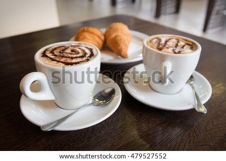 Two cups of hot cappuccino and croissants in cafe