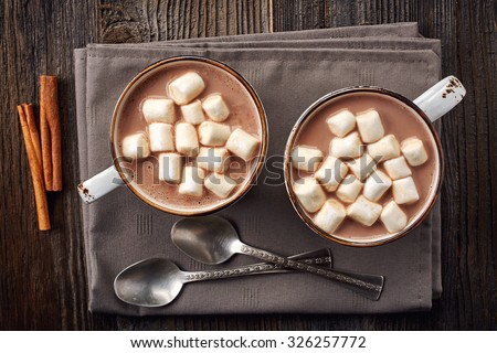 Two cups of hot cocoa with marshmallows and cinnamon sticks on wooden background - stock photo