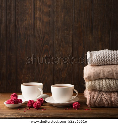 Two cups of hot tea, strawberry chocolate candies and Stack of cozy knitted sweaters on rustic dark wooden background. Valentine's day celebration concept. Winter time.