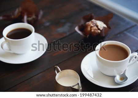 Two cups of plain coffee with muffins beside them on a dark wood table - stock photo