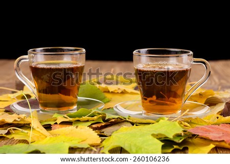 Two cups of tea on a wooden table with autumn leaves
