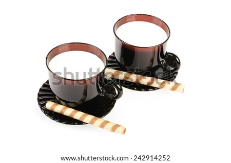 Two cups with milk and cookies. Isolated over white - stock photo
