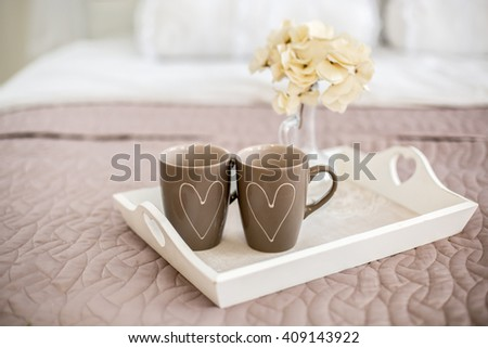 Two cups with painted hearts.Blank heart shaped card and flowers with breakfast served in bed. Extreme shallow depth of field with selective focus on heart. - stock photo