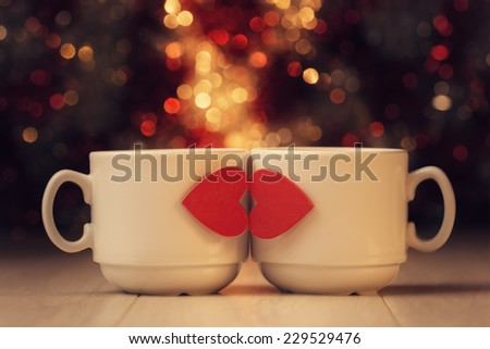 Two cups with red hearts on wooden table against defocused lights. - stock photo