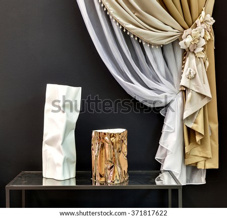 two curtains with decorative pickup with flowers and two vases on a table - stock photo