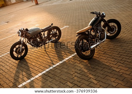 Two custom vintage motorbikes cafe racer black and silver motorcycle directed in opposite directions on empty rooftop parking lot during sunset. Confrontation of urban styles. Hipster lifestyle.