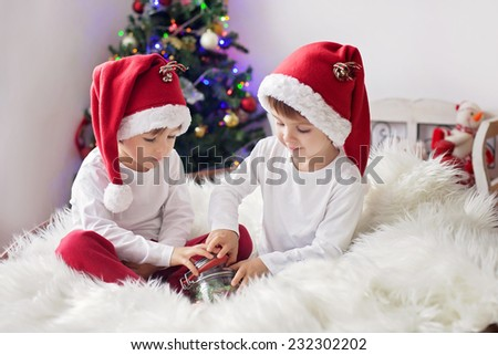 Two cute adorable boys enjoying candies at christmas time in front of the christmas tree - stock photo
