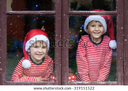Two cute boys, brothers, looking through a window, waiting impatiently for Santa - stock photo
