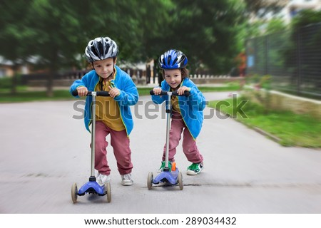 Two cute boys, compete in riding scooters, outdoor in the park, summertime - stock photo