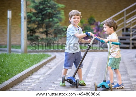 Two cute boys, compete in riding scooters, outdoor in the park, summertime. Kids are happy playing outdoors. Two brothers standing on their scooters.