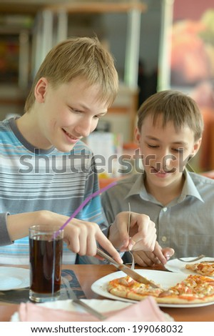 Two cute boys eatning pizza in cafe