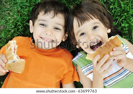 Two cute boys laying on ground in nature and happily eating healthy food - stock photo