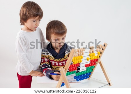 Two cute boys, learning to count and math, playing at home with abacus, isolated on white - stock photo