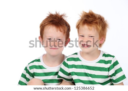 Two cute brothers dressed in green and white stripes smiling and playing