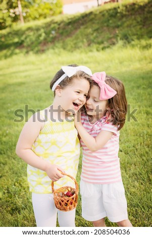 Two cute Caucasian little sisters hugging and laughing outdoors. To child friends having fun playing in park on sunny summer day wearing pastel color clothes and bow headbands.  - stock photo