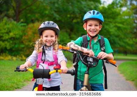 Two cute children cycling in summer park - stock photo