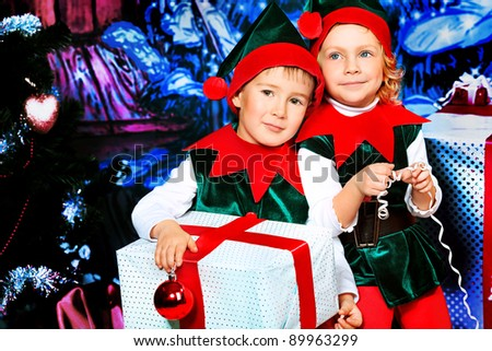 Two cute children in christmas elf costumes posing over christmas background. - stock photo