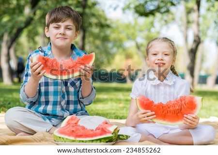 Two cute children in park eating juicy watermelon