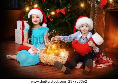 Two cute children in Santa hats sitting with gifts by the Christmas tree at home. The magic of Christmas. - stock photo