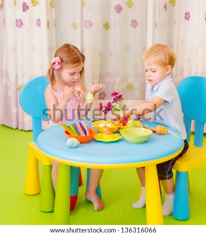 Two cute children paint Easter eggs on art lesson in daycare, handmade decoration for Christian holiday - stock photo