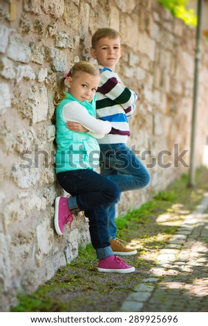 Two cute children standing near the stone wall - stock photo