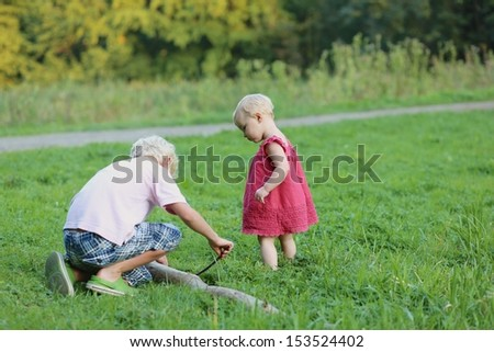 Two cute children, teenager boy with his pretty little baby sister are playing together in the nature