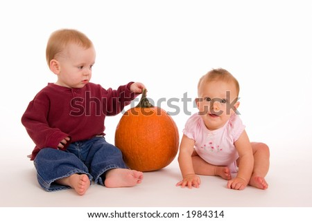 Two cute children with a pumpkin, timely for Halloween or any Autumn theme. Older boy is looking at younger girl. - stock photo