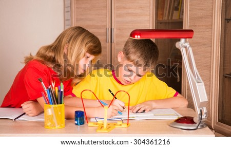 Two cute children working on their homework together. Boy and girl doing homework at home. - stock photo