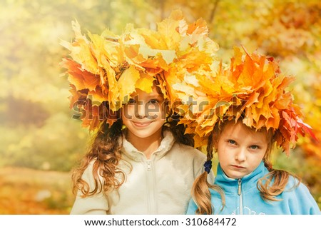 Two cute embracing friends in a yellow autumnal park  - stock photo