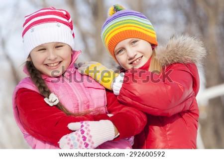 Two cute girls having fun in winter park - stock photo