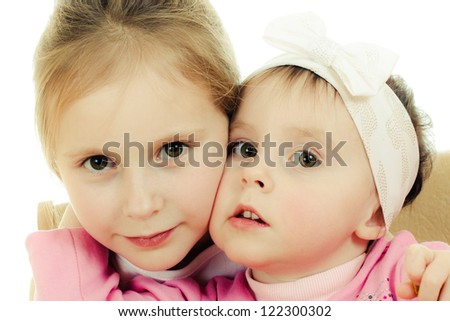Two cute girls hugging on white background. - stock photo