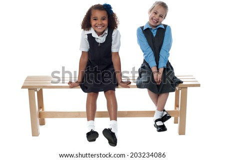 Two cute girls laughing sitting on a bench - stock photo