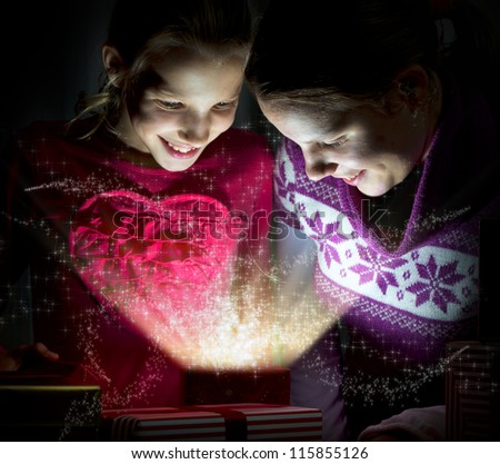 Two cute girls looking inside of a magical present - stock photo