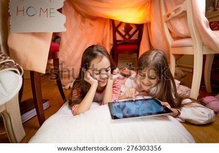 Two cute girls lying on floor at bedroom and playing on digital tablet - stock photo