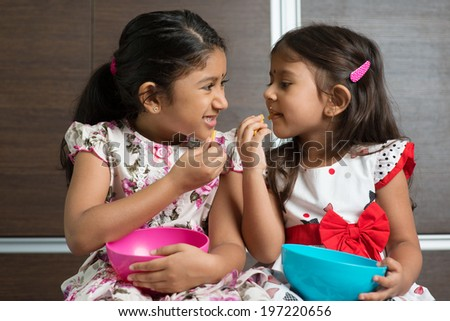 Two cute Indian girls eating murukku. Asian sibling or children living lifestyle at home. - stock photo