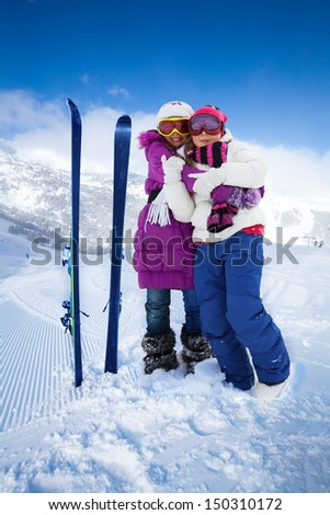 Two cute kids girls hugging with skis and mountain on background - stock photo