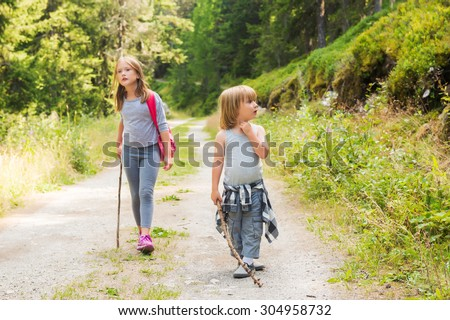 Two cute kids hiking in forest - stock photo